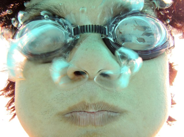 closeup man face with swimming goggles