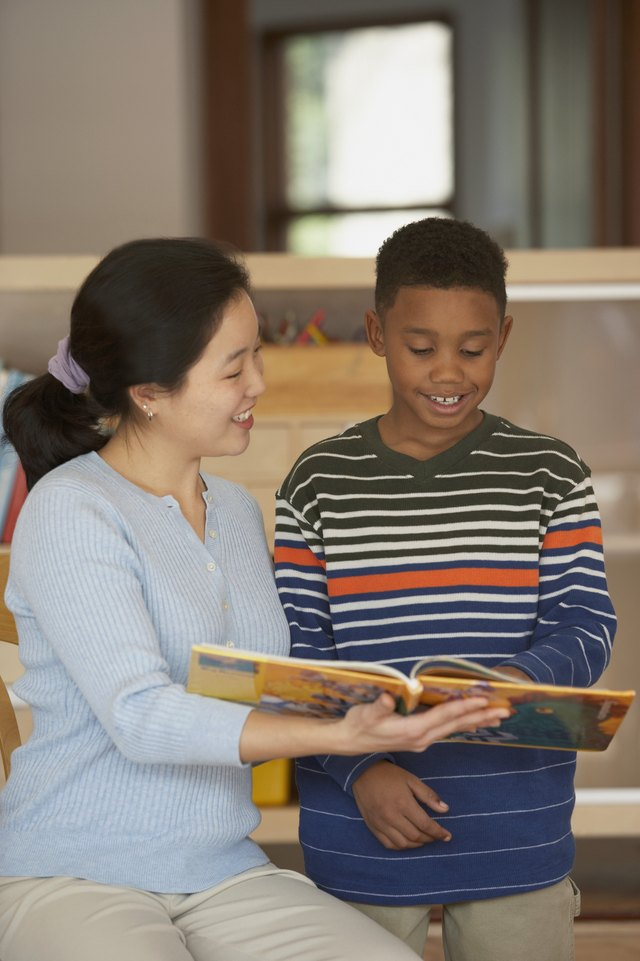 Female teacher and her student reading a book