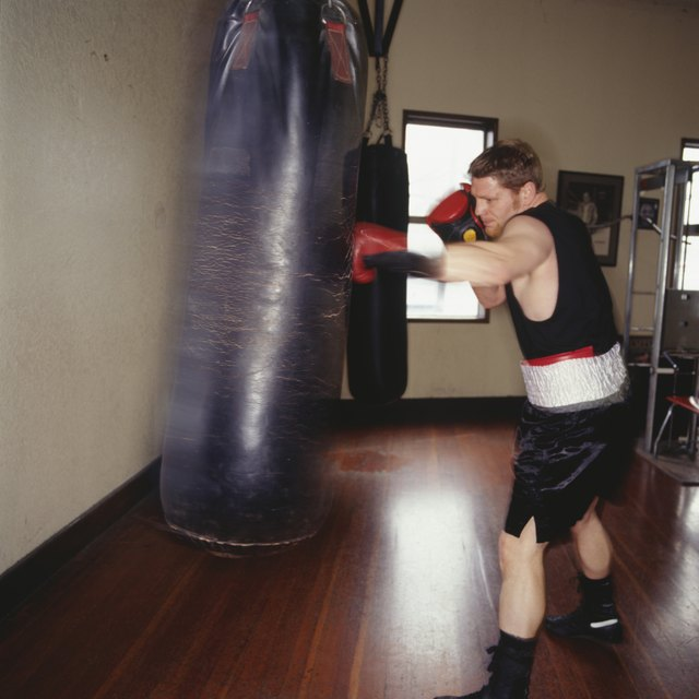 Boxer training with punch bag in gym, side view