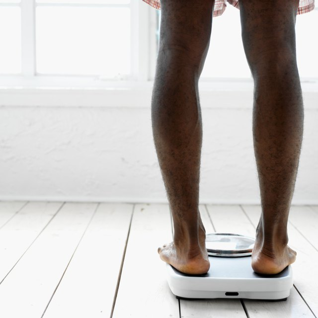 Close-up of the legs of a young man standing on a weighing scales