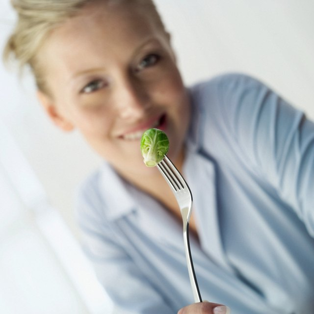 Portrait of woman holding a Brussels sprout on a fork