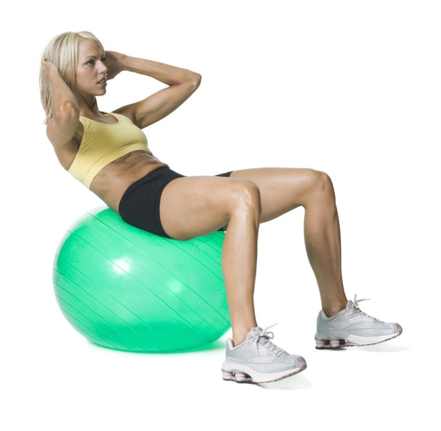 full body shot of a young woman in a yellow and black exercise outfit as she does sit ups on a green ball