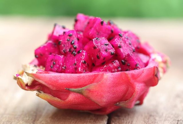 Pieces of dragon fruit on wooden surface
