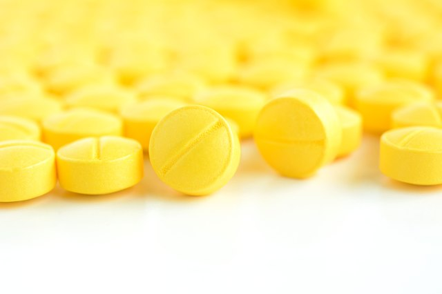 Closed up of small yellow medicine tablets (or pills)
