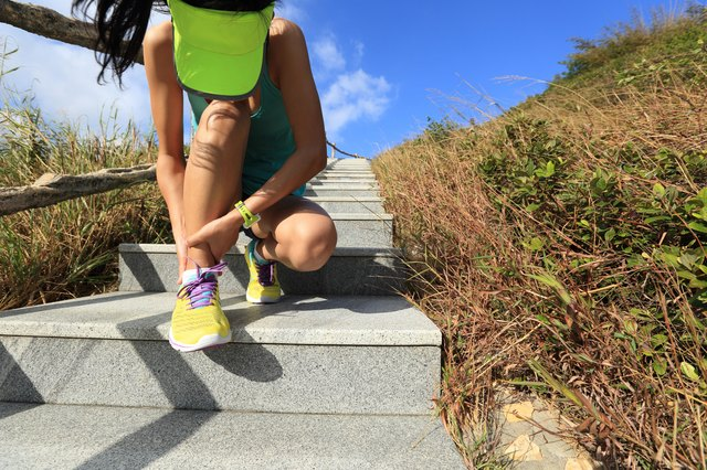 young woman runner hold her sports injured ankle