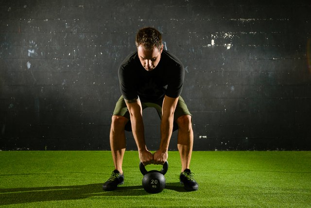 Athlete lifting heavy weight with Kettle-bell