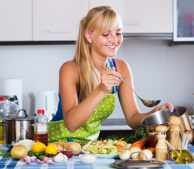Young woman cooking vegetables