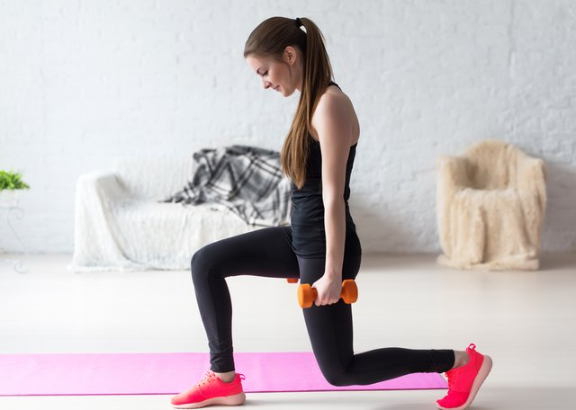 Athletic woman warming up doing weighted lunges with dumbbells workout