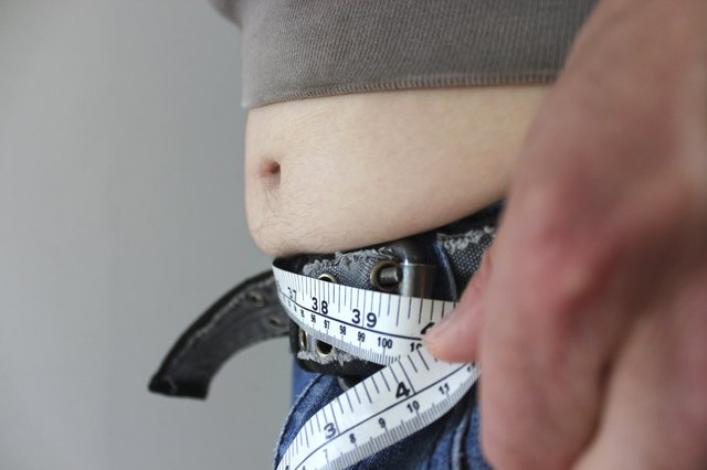 Overweight man with a fat tummy spilling over jeans, measuring