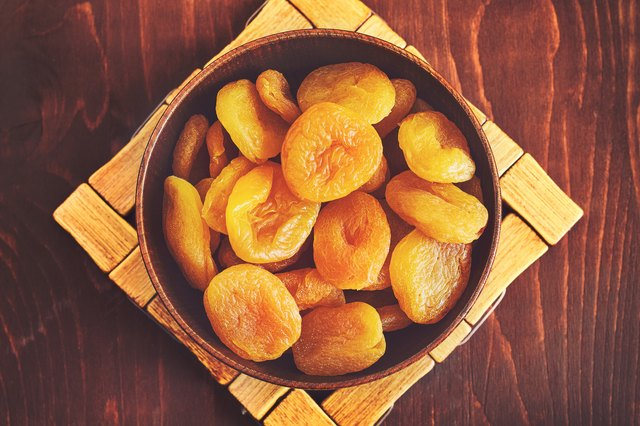 Dried apricots on wooden background