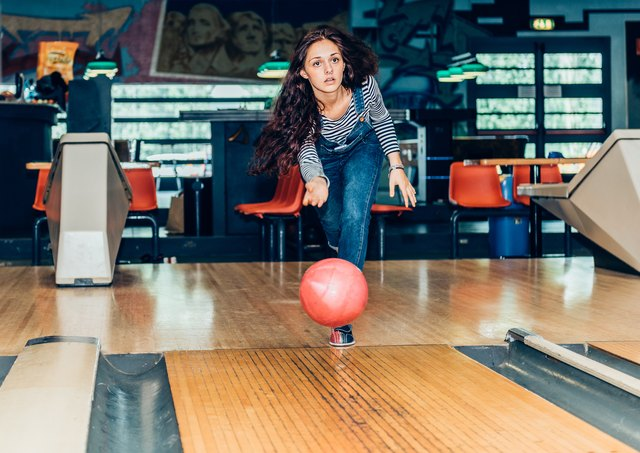 young girl plays bowling