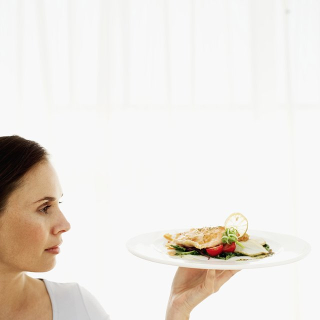 Young woman holding up a plate of grilled salmon