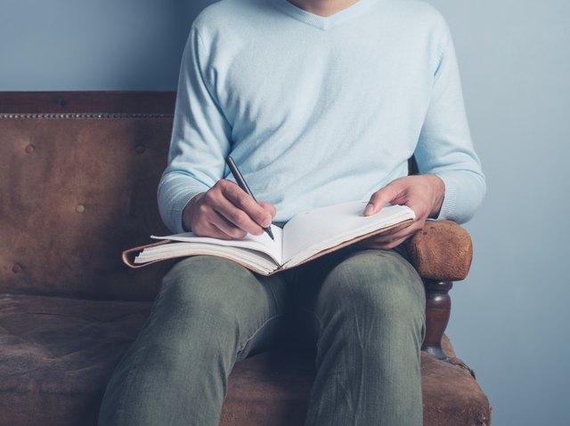 Man writing progress in journal.