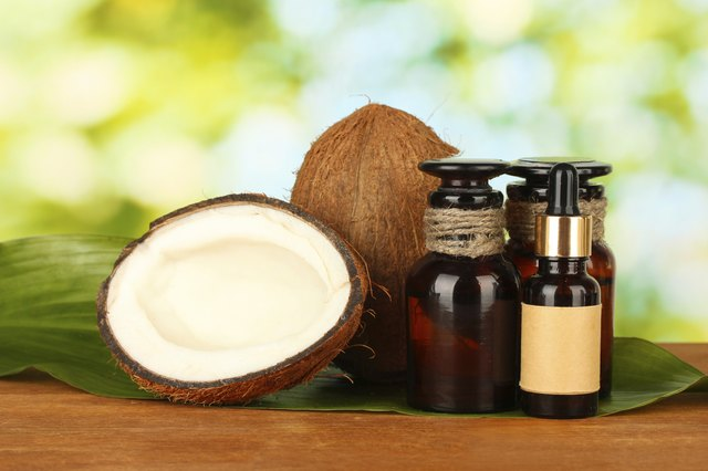 coconut oil in bottles with coconuts on green background