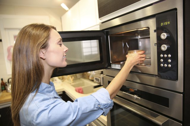 Woman using a microwave in kitchen