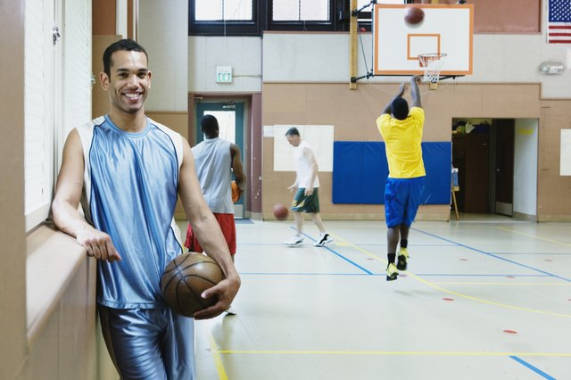 Portrait of a young man holding a basketball in a basketball court