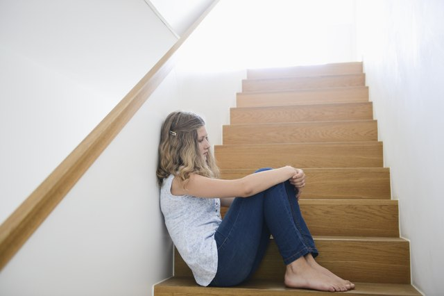 Girl sitting alone on wooden staircase