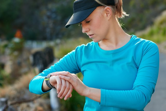 Fit, caucasian woman checking the time during a training run