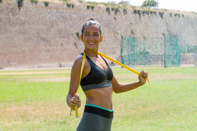 Female water sprinkled wet athlete woman in sportswear measuring her waistline, hips and chest after a workout at an outdoor field stadium. Healthy lifestyle sports and fitness concept.