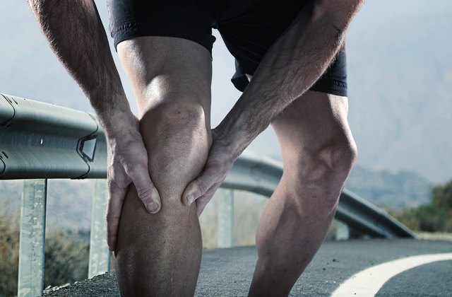 runner with athletic legs holding knee suffering muscle pain
