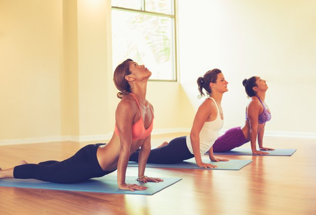 People Practicing Cobra Pose in Yoga Class