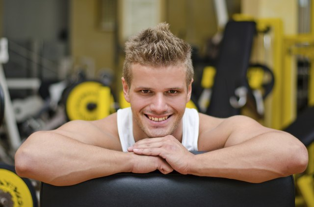 Attractive young man in gym resting on equipment