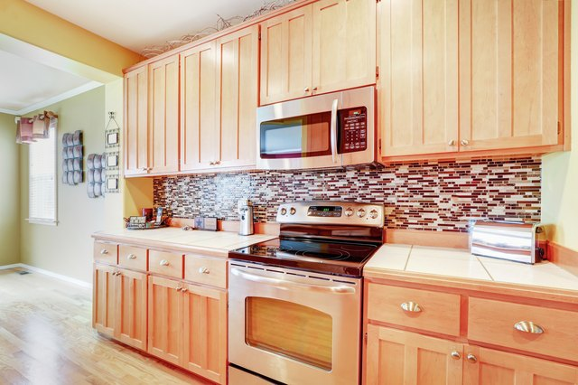 Light wood cabinets with multicolored backsplash