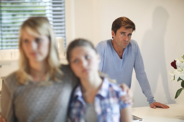 Mature man watches mother and daughter in kitchen
