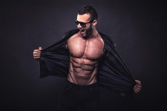 Crazy fit man posing in studio.