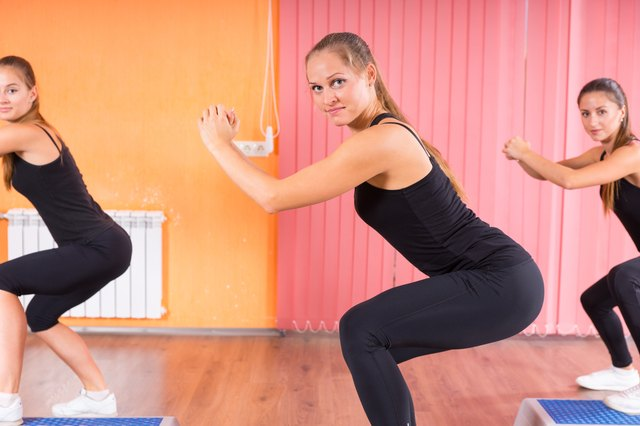 Pretty Women in Squatting Exercise inside the Gym