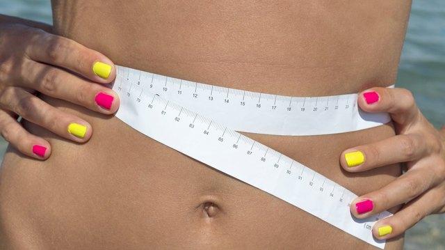 Girl measuring her waist at the seaside