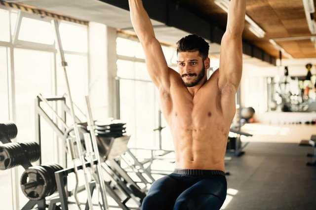 Abs workout by handsome man in gym