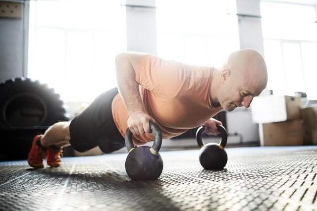Active young man doing push-ups with kettlebells
