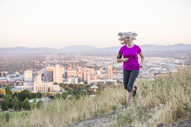 Caucasian woman running on hilltop over Salt Lake City, Utah, United States