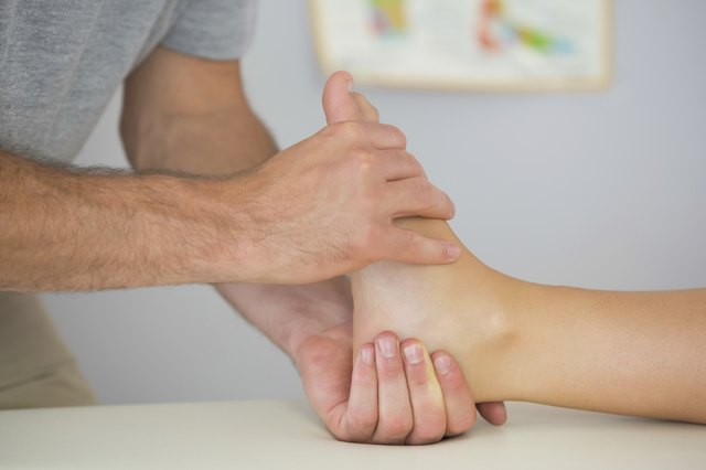 Physiotherapist controlling patients foot