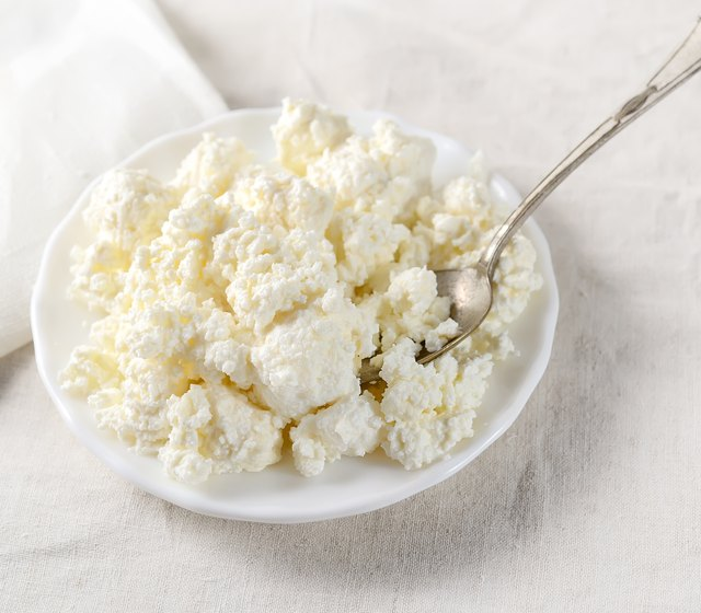 Plate of homemade cottage cheese on white tablecloth.