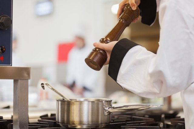 Chef adding pepper to soup