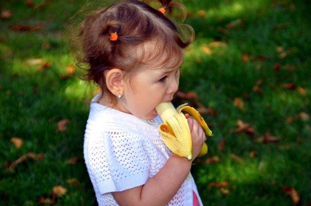 little girl eating a banana in summer outdoors