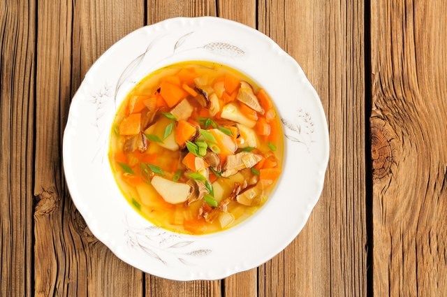 Porcini mushroom soup with potato and carrot in white plate