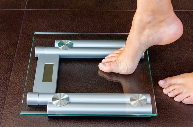 Closeup of woman foot uploading to bathroom scale