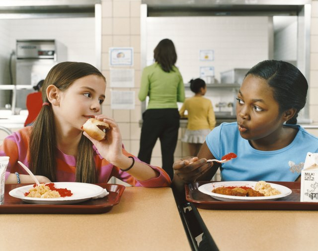 Two Schoolgirls Sitting at a Table in a Canteen Eating Their Lunch
