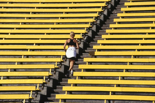 Woman running up stairs in stadium, rear view