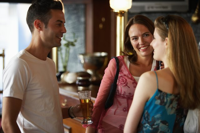 Young man talking to two women at bar, holding glass of beer, smiling
