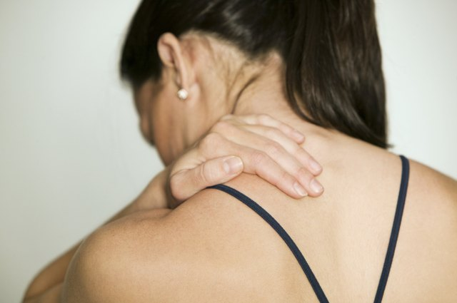 Woman massaging shoulder, in studio, rear view