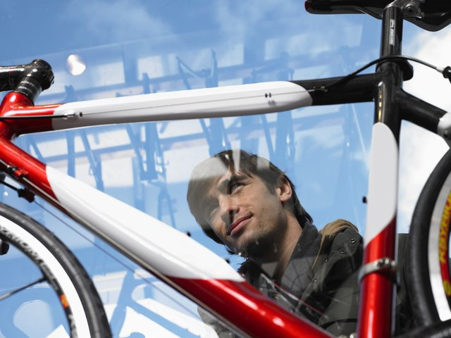 Man looking at bicycle, low angle view through glass