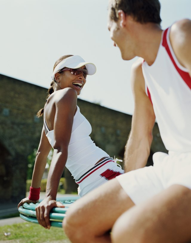 Couple in fitness clothes, woman smiling (focus on woman)