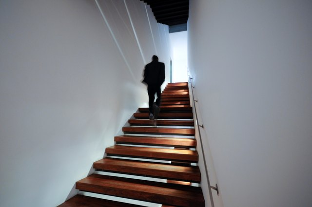 Silhouette figure waling up stairs.
