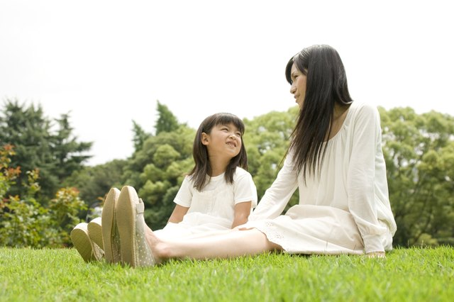 Mother and daughter sitting outside together on a lawn