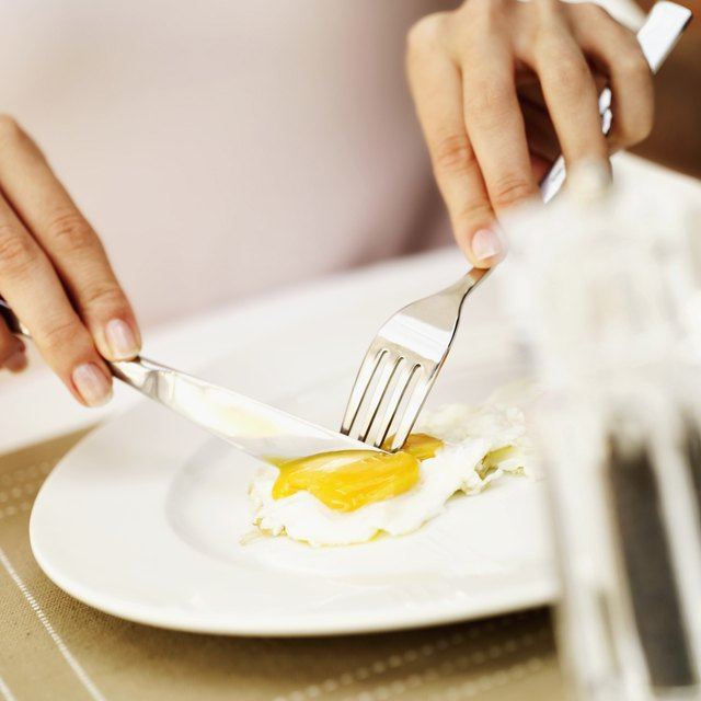 Close-up of a woman's hands cutting a fried egg with a fork and knife
