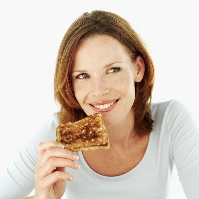 Young woman smiling eating a slice of toast